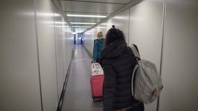 Aeropuerto Dos mujeres jovenes que corren en su vuelo Muchacha rubia con una maleta a toda prisa a pasar a través del tubo a almacen de video
