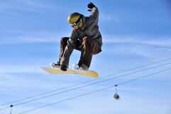 Aeroski: snowboarder touches his board Royalty Free Stock Images