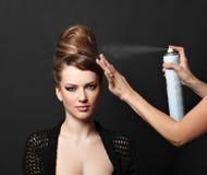 Aerosol de pelo, mujer sobre negro Imágenes de archivo libres de regalías