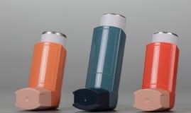 Aerosol mit drei Inhalatoren auf grauem Hintergrund Stockbilder