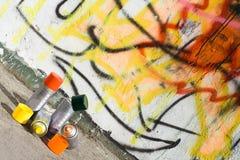 Aerosol paint and graffiti painted wall. Aerosol paint on the ground near graffiti painted wall Stock Photography