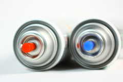 Aerosol Spray Paint Cans. A photo of the tops of two aerosol spray paint cans laying on their sides Stock Image