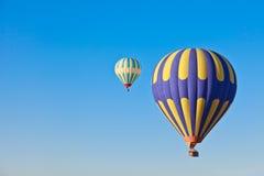 Aerostati di aria calda che vanno alla deriva attraverso un cielo blu Fotografia Stock