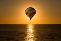 Aerostatischer Ballon im Meer auf einem Sonnenaufgang Stockbild