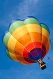 Aerostato caldo che galleggia in cielo blu fotografia stock