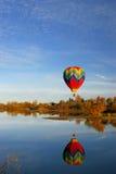 Aerostato di aria calda sopra il lago Fotografia Stock