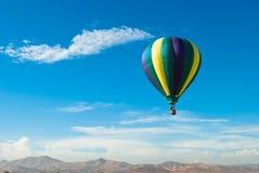 Aerostato di aria calda sopra le montagne Immagine Stock