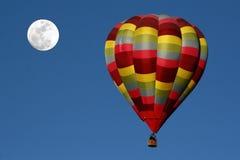 Aerostato e luna di aria calda nel cielo di primo mattino Immagini Stock