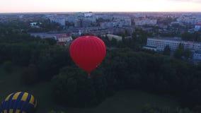 Aerostato rovente che galleggia sopra l'area verde della città all'alba, volo iniziale di festival stock footage