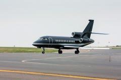 Aerotaxi nero che rulla dalla pista Immagine Stock