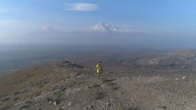 Aerial view: man running at trail around mountains. Aerovideo high above of beauty autumn cliff ridge in Armenia. Successful stylish man in colorful coat quick stock footage