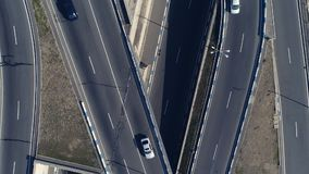 Aerial view of cityscape curve roads with cars. Aerovideo: unmanned aircraft flying over free interstate expressway with machines at autumn day. The modern stock video