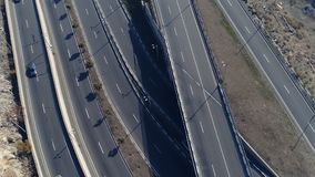 Aerial view of cityscape curve roads with cars. Aerovideo: unmanned aircraft flying over free interstate expressway with machines at spring day. The modern stock video