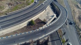 Aerial view of cityscape curve roads with cars. Aerovideo: unmanned aircraft flying over free interstate expressway with machines at summer day. The modern stock footage