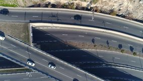 Aerial view of cityscape curve roads with cars. Aerovideo: unmanned aircraft flying over free interstate expressway with machines at summer day. The modern stock video footage