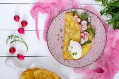 AES is currently down for maintenance. Please try again later. Useful french breakfast: radish salad and arugula, egg poached on a thin crape on a ceramic plate Stock Photos