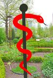 Aesculapius symbol in a garden with natural medicinal plants  Stock Image