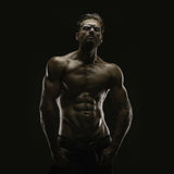 Aesthetic bodybuilding. Handsome athletic young aesthetic man isolated on black Stock Photos