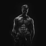 Aesthetic bodybuilding. Handsome athletic young aesthetic man isolated on black. Black and white Stock Image