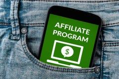 Afílie o conceito do programa na tela do smartphone no bolso das calças de brim imagens de stock royalty free