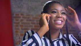 Af van het close-upgezicht fijn Afrikaans wijfje dat over telefoon naast rode laptop binnen bureau spreekt stock footage