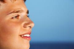 afar mot pojken som ser den le tonåringen för hav fotografering för bildbyråer