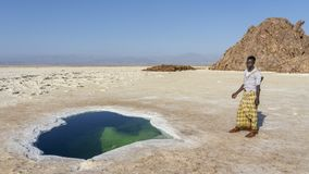 Afar soldier near a salty pond in the plain of salt in the Danakil Depression in Ethiopia in Africa. stock photos