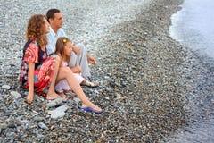 afar strandfamiljflicka som ser sitta royaltyfri foto
