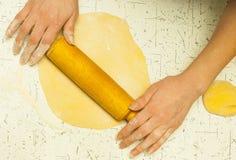 Afdekkend deeg De handen van vrouwen houden deegrol en floured Het bakken in keuken Stock Foto's