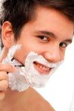 Afeitados del hombre con una hoja de afeitar y una crema de afeitar fotos de archivo
