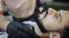 Afeitar el proceso de barbas en barbería El amo hace a un cliente de la barba del corte de pelo con la maquinilla de afeitar rect almacen de video