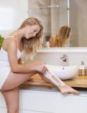 Afeitar las piernas Imagen de archivo libre de regalías