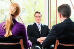Affär - jobbintervju med timme och sökanden royaltyfri foto