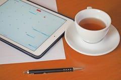 Affär kalendrar, tidsbeställning Kontorstabell med notepaden, dator, kaffekopp Fotografering för Bildbyråer