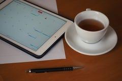 Affär kalendrar, tidsbeställning Kontorstabell med notepaden, dator, kaffekopp Arkivbild