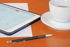 Affär kalendrar, tidsbeställning Kontorstabell med notepaden, dator, kaffekopp Arkivfoton
