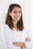 Affär: nöjd nätt brunettkvinna med vikta armar i en wh Arkivfoto