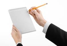 Affär och reporterämne: handen av en journalist i en svart dräkt som rymmer en anteckningsbok med en blyertspenna på en vit bakgr Royaltyfri Fotografi