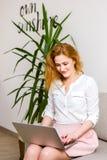 Affär och utbildning använder den Caucasian kvinnan för härligt ungt rött haired långt hår bärbara datorn, medan sitta på soffan  arkivfoton