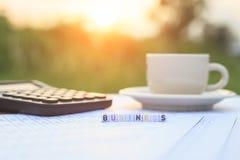 Affär som är skriftlig i bokstavspärlor och en kaffekopp på tabellen Royaltyfri Bild