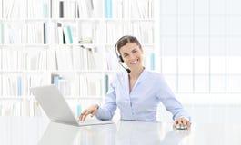 Affär som ler kvinnan eller en kontorist som arbetar på hennes intelligens för kontorsskrivbord arkivbild