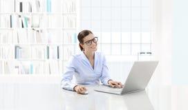Affär som ler kvinnan eller en kontorist som arbetar på hennes intelligens för kontorsskrivbord arkivfoto