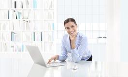 Affär som ler kvinnan eller en kontorist som arbetar på hennes intelligens för kontorsskrivbord royaltyfria bilder