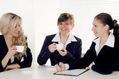affär som sitter tre kvinnor Arkivbild