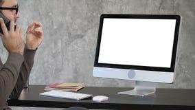 Affär, stopptid och teknologibegrepp - man med datoren som kallar på smartphonen och pekar till bildskärmen vitt arkivfilmer