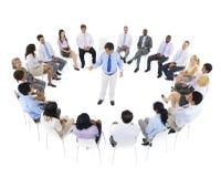 Affär Team Sitting runt om ledaren Arkivbild