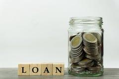 Affären och det finansiella planbegreppet för lån, intecknar, besparingen och investeringen En bunt av mynt i exponeringsglaskrus royaltyfri foto