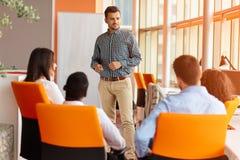 Affären, starten, presentationen, strategi och folkbegreppet - man danandepresentationen till det idérika laget på kontoret royaltyfri fotografi