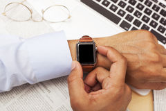 Affärer mans genom att använda en smart klocka med kopieringsutrymme Arkivbild