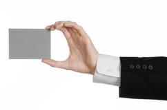 Affärs- och advertizingämne: Man i den svarta dräkten som rymmer ett grått tomt kort i handen som isoleras på vit bakgrund i stud Arkivfoto